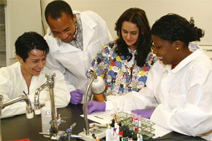 MDC's Rosa Castro, an assistant professor of clinical laboratory technology (center, in multi-colored scrubs) works with Maria Rabello (the students' tutor and translator); and student biologists from Mozambique, Martins Muloiua and Isabel Pinto.