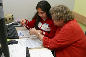 Volunteer helping a lady to file her taxes