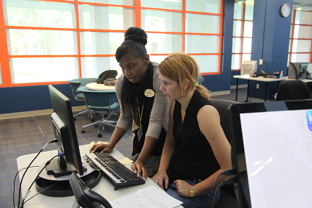 MDC faculty assisting student on a PC